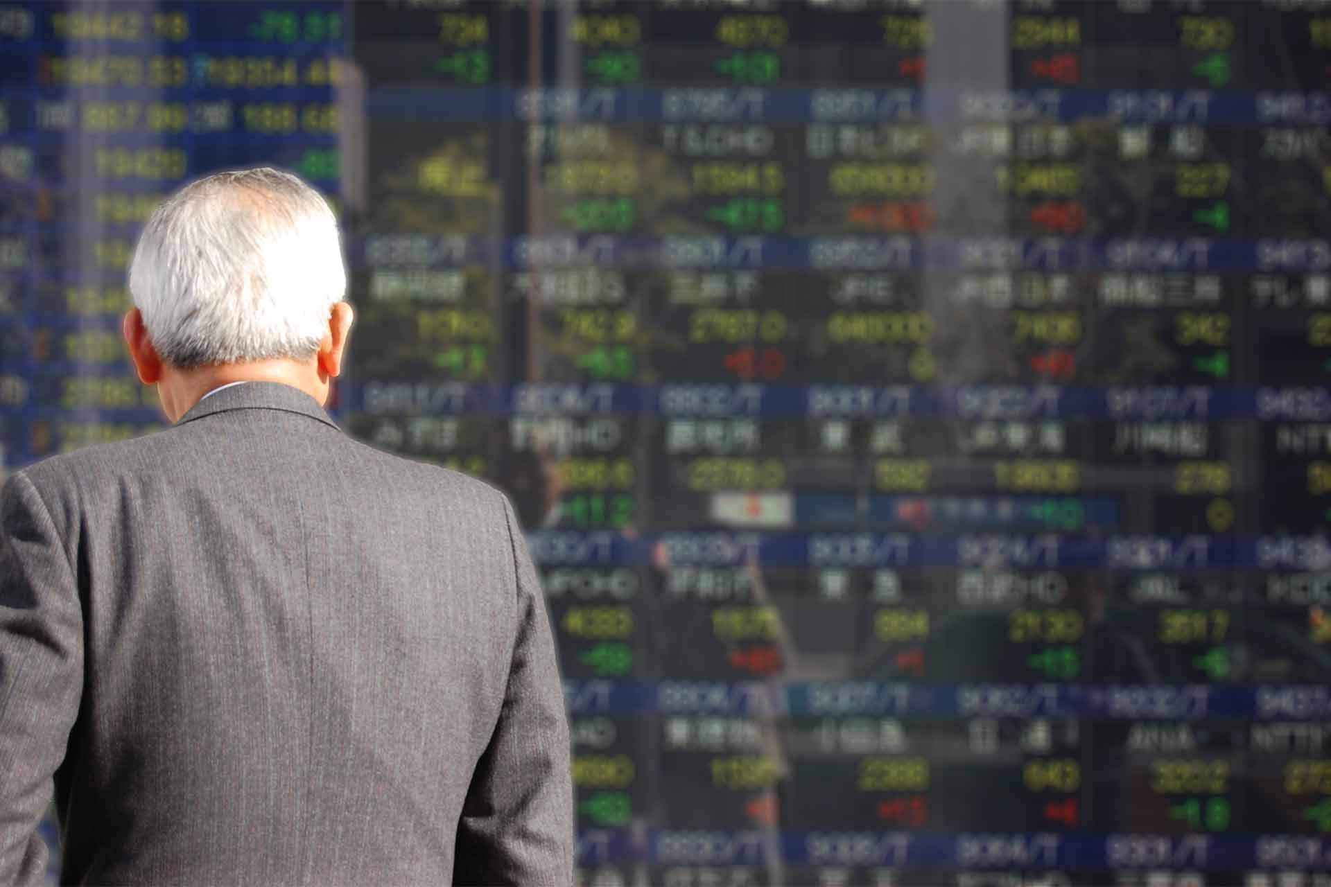 株価ボードを見る男性