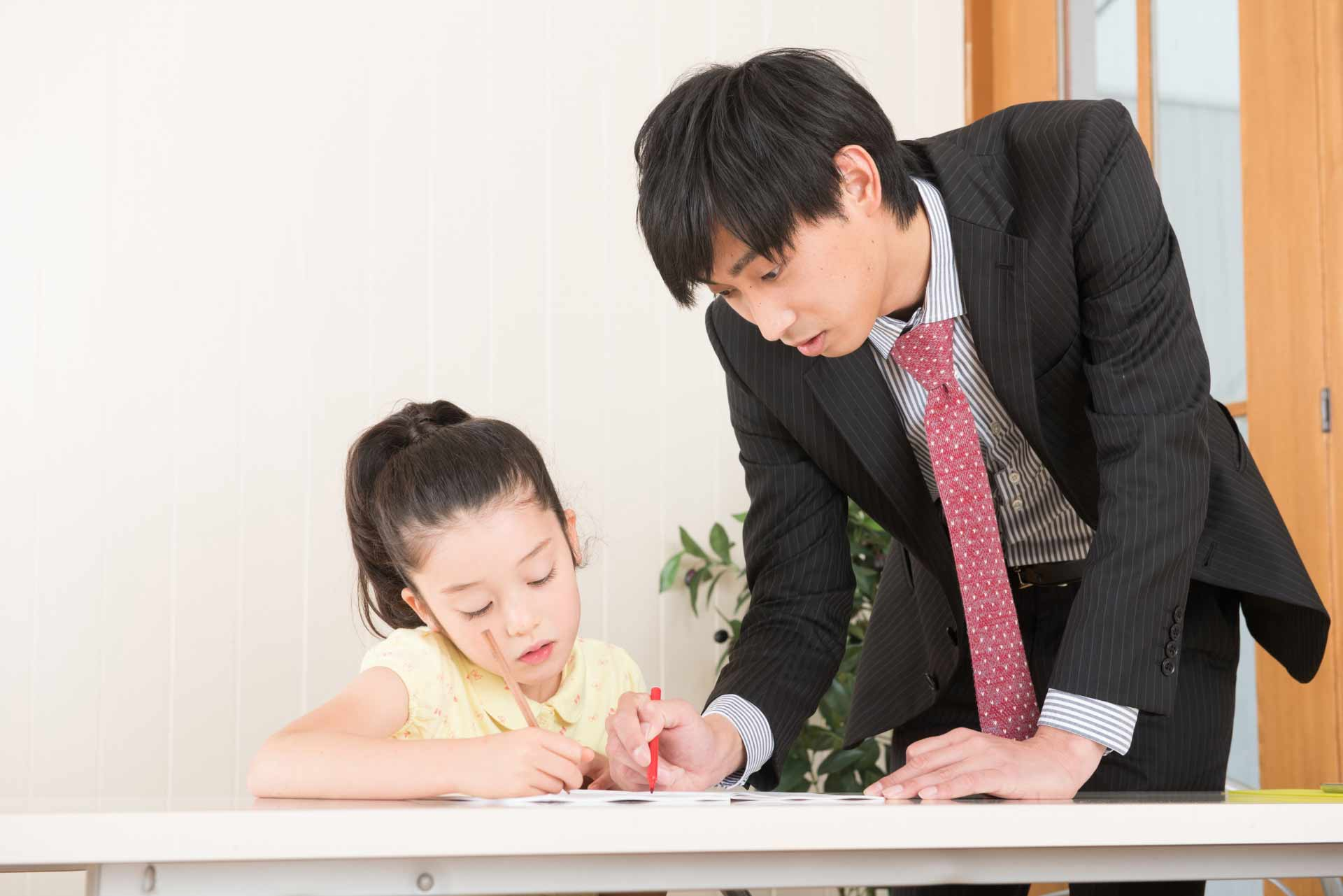 家庭教師に勉強を教わる子供